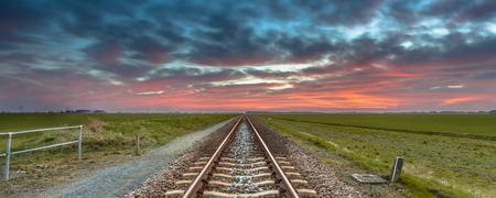 ferrocarril: Ferrocarril interminable viaje hacia el horizonte bajo un cielo azul y rojo como un concepto para el cielo y la libertad.