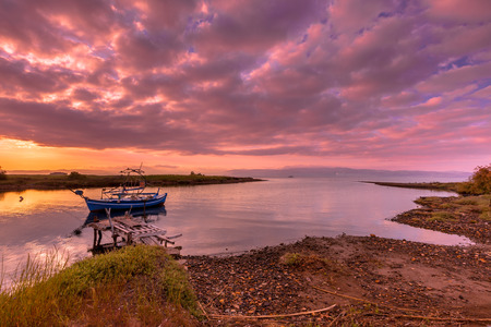 inlet bay: Fishing boat in a river inlet bay during colorful sunrise on Lesbos island, Greece