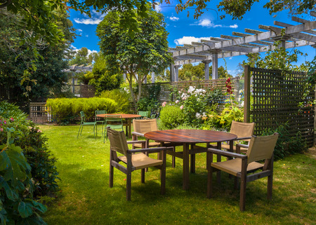 Home backyard with garden table set in sunny a lush garden with shade of trees Archivio Fotografico