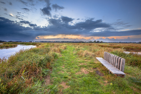 fantastic view: Inviting modern seat with fantastic view over marshland in the Netherlands Stock Photo