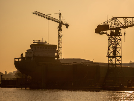 shipway: Back lit Silhouette of a Ship Being Constructed on a Wharf in the Netherlands