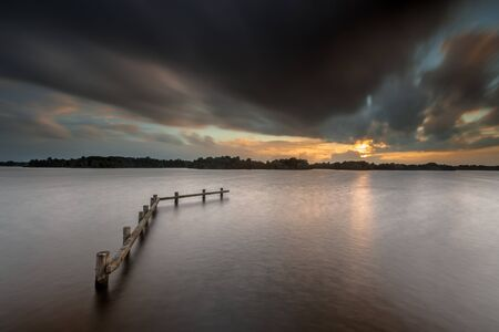 enlightment: Conceptual Mood Concept Dark lake landscape during sunset on a rainy stormy day