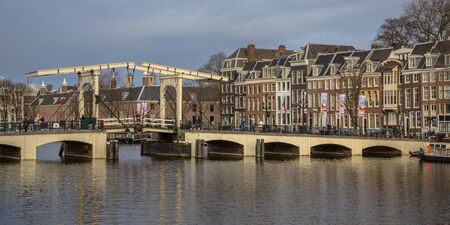 canal houses: Traditional bridge Magere brug over the Amstel with colorful traditional canal houses in Amsterdam Stock Photo