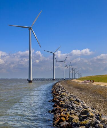 positioned: Long row of wind turbines positioned in water offshore along the coast