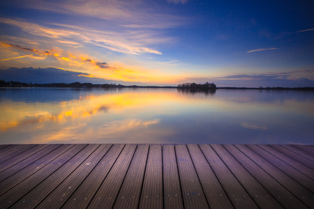 Brand new wooden recreational swimming deck on the lakeside during spectacular sunset over water.