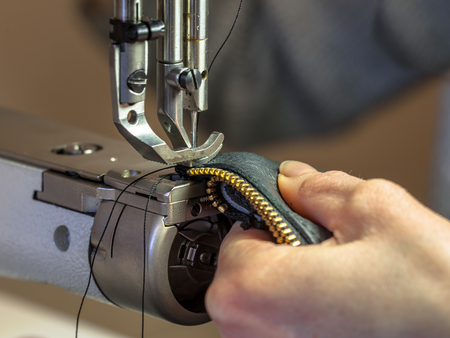 Leather sewing machine in action with hands working on a shoulder bag