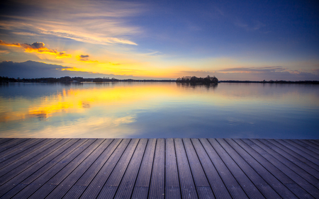 pier: Wooden recreational swimming deck on the lakeside during spectacular sunset over water Stock Photo