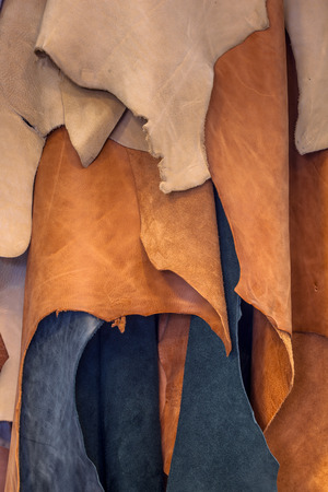 leather background: Pieces of leather in natural colors in a design workshop