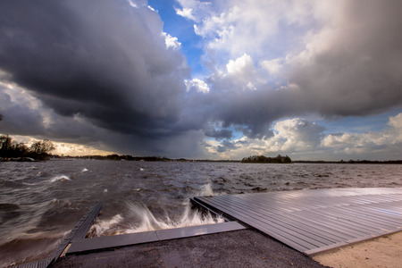 storms: Harsh wind dark clouds and moderate high waves breaking on a landing stage when a storm is coming in over a Dutch lake Stock Photo