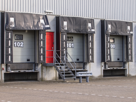 loading dock: Three Empty Loading Dock Cargo Doors as a concept for Economic Growth Stock Photo