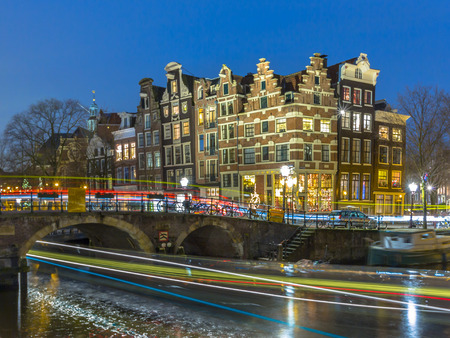 canal houses: Night shot of Colorful traditional canal houses with passing tour boats and cars on the corner of brouwersgracht