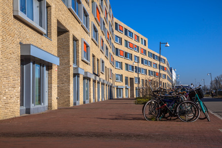 condo: Modern apartment block with light bricks and orange sun screens in a suburban neighbourhood with bicycles parked in front