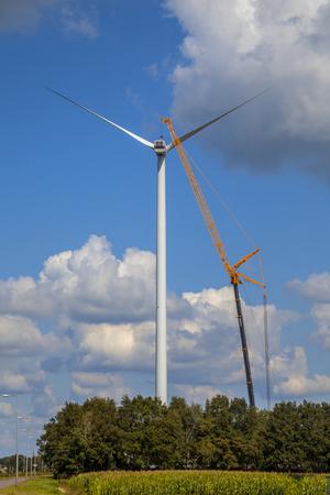 Giant windturbine wordt onderhouden door een grote kraan voor reparatie Stockfoto
