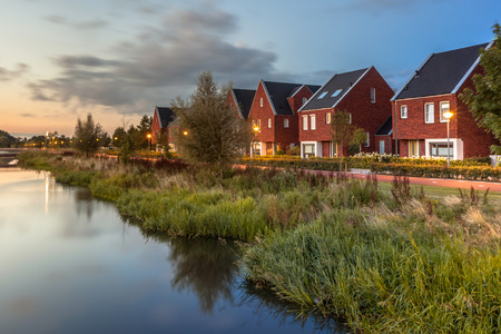 eco house: Long exposure night shot of a Street with modern ecological middle class family houses with eco friendly river bank in Veenendaal city, Netherlands. Stock Photo