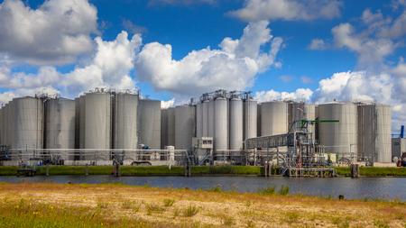 negocios comida: Estación industriales de tamaño medio tanque de almacenamiento con instalaciones de atraque en el puerto de Amsterdam Editorial