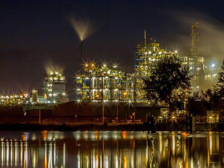 paesaggio industriale: scena notturna di dettaglio di un impianto industriale pesante chimica con tubi e luci che riflettono in acqua Archivio Fotografico
