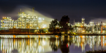 industria petroquimica: Panorama Night scene of detail of a heavy Chemical Industrial plant reflecting in water with mazework of pipes in twilight Foto de archivo