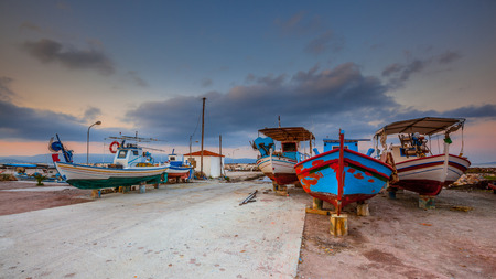 summer holidays: Fishing harbor scene. Boats being repaired in a traditional greek village harbor on a beautiful summer morning in july Stock Photo