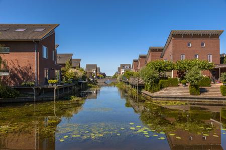 middle class: Calle de casas ecológicas familia de clase media en la orilla del río en Kloosterveen, Assen Países Bajos