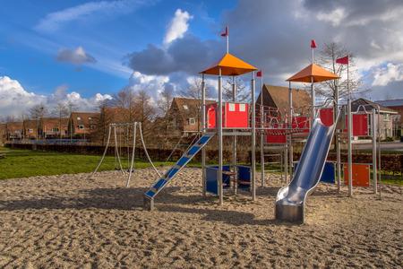 superficie: Parque infantil metal moderno colorido en la par del suburbio para familias de Eelderwolde, Groningen