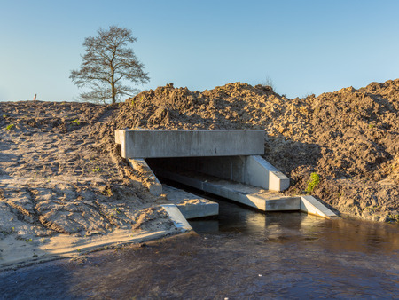 frill: Newly constructed Eco Friendly Culvert with walking strip for animals above the waterline serving as a wildlife crossing Stock Photo
