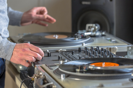 record: Hands of DJ mixing music from vintage long play  records in his studio at home