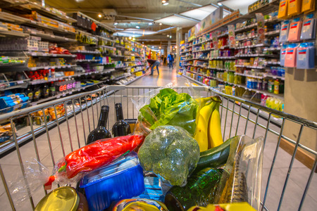 Grocery cart at a supermarket aisle filled up with food products seen from the customers point of view