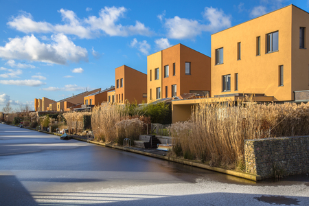 waterfront: Modern geometric family houses along a canal in winter setting, Groningen, Netherlands