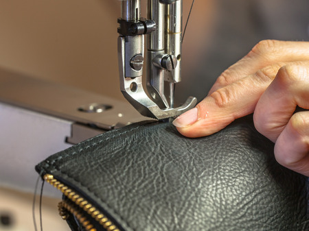 Leather sewing machine in action in a workshop with hands working on a shoulder bag