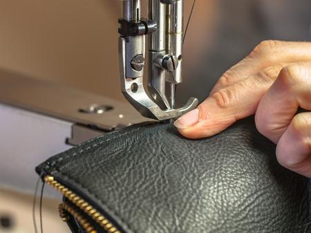 Leder-Nähmaschine in Aktion in einem Workshop mit den Händen auf einer Umhängetasche Arbeits