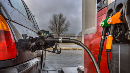 fuelling pump: Gas station car refueling close up on a rainy februari day with dark colors in the Netherlands Stock Photo