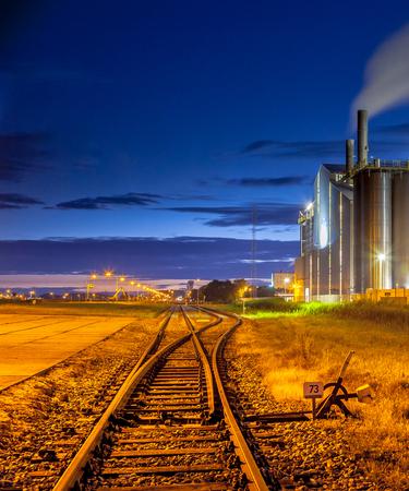 superficie: Escena nocturna del interruptor del ferrocarril en un área industrial pesada de la química con los colores y las luces soñadores místicos en crepúsculo