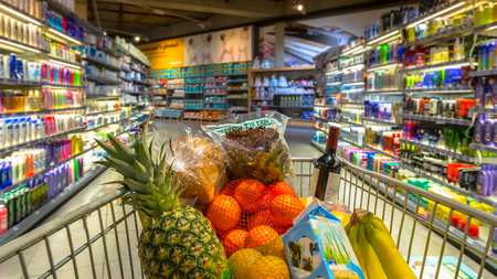 convenient store: Easter shopping Grocery cart at a colorful supermarket filled up with food products as seen from the customers point of view Stock Photo