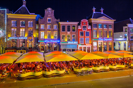GRONINGEN, THE NETHERLANDS-MAY 5,2015: Students on teracces in the night. Famous bars and restaurants in the old center of the university town of Groningen. The Grote Markt is famous for its nightlife for students 스톡 콘텐츠