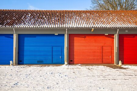 garage doors: Red and Blue Fire Brigade Garage Doors and Frost roads service next to each other on a Snowy Winter Day Stock Photo
