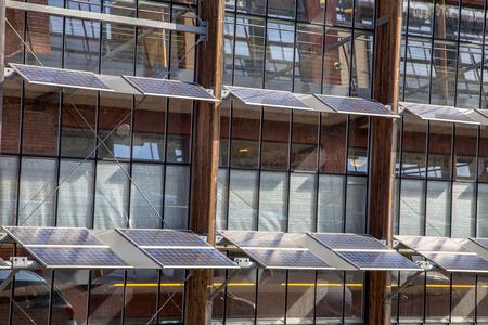 地球温暖化の解決策として事務所ビルの正面に太陽電池パネルを使用しての代替方法