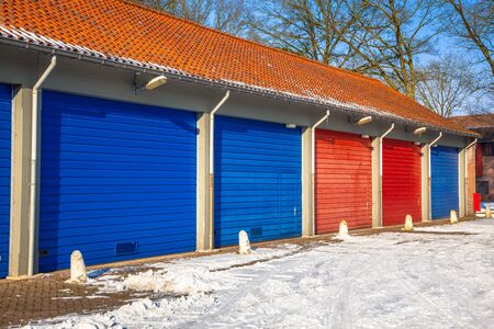 garage doors: Fire Brigade and Frost roads service Garage Doors in blue and red next to each other on a Snowy Winter Day