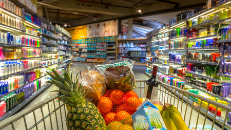 Easter shopping Grocery cart at a colorful supermarket filled up with food products as seen from the customers point of view Stockfoto