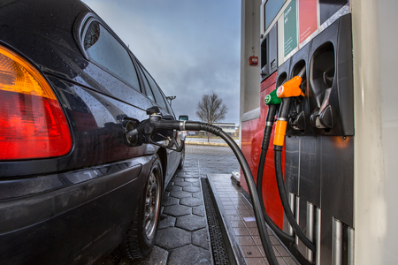 fuelling pump: Gas pump fill at a gas station car close up on a rainy februari day with dark colors in the Netherlands