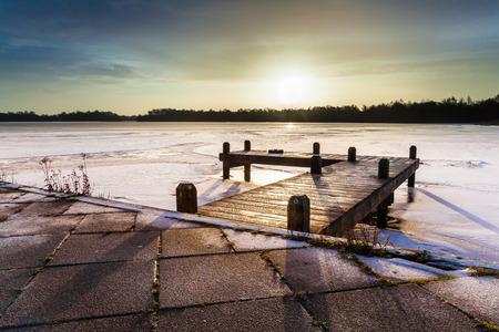 winter sunrise: Winter Landscape with Lake with jetty covered with ice under amber Colored Sunrise Stock Photo