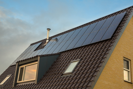 inconspicuous: Discrete solar panels in the same color as roof tiles and dormer on a house