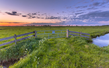 dutch: Purple sunset over fence in dutch polder landscape near Groningen