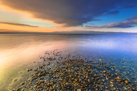 the four elements: Colorful symmetrical sunrise at the mediterranean island of Lesbos, Greece Stock Photo