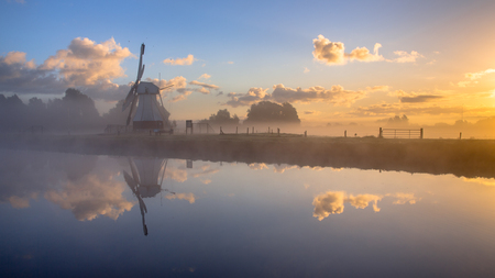 fog white: White Historic windmill in morning fog reflected in river under beautiful sunrise, Drenthe, Netherlands