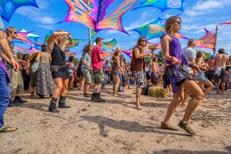 LEEUWARDEN, NETHERLANDS-AUGUST 30, 2015: Colorful party people dancing on the sandy dancefloor during daytime on Psy-Fi open air psychedelic trance music Festival