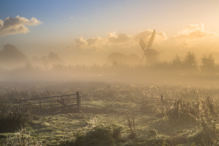 Morning fog over farmland with gate in foreground and wooden windmill in background Reklamní fotografie