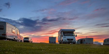 Roulotte e auto parcheggiate su un campeggio erboso in estate sotto bel tramonto Archivio Fotografico - 53000557