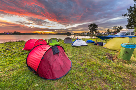 Camping spot with dome tents near lake on a music festival camp site under beautiful sunrise Archivio Fotografico