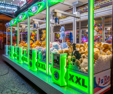 GRONINGEN, THE NETHERLANDS-MAY 5, 2015: Arcade crane vending machine with colourful green lights on the annual funfair on central square.