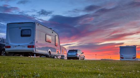 Roulotte e auto parcheggiate su un campeggio erboso in estate sotto bel tramonto Archivio Fotografico - 53005945